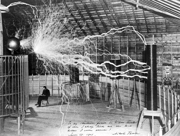 Ο Νικολά Τέσλα στο εργαστήριό του, στο Κολοράντο Σπρινγκς, μπροστά στον ασύρματο πομπό μεταφοράς ενέργειας