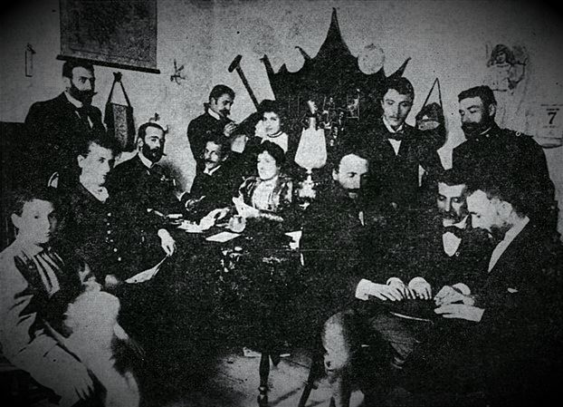 Πνευματιστική συγκέντρωση στο σπίτι του Γεωργίου Σουρή. Γύρω από το τραπεζάκι διακρίνονται, από αριστερά, οι Γεώργιος Σουρής, Μπάμπης Άννινος και Γεώργιος Δροσίνης. Όρθιοι δεξιά, ο Νικόλαος Επισκοπόπουλος και ο Ανδρέας Καρκαβίτσας