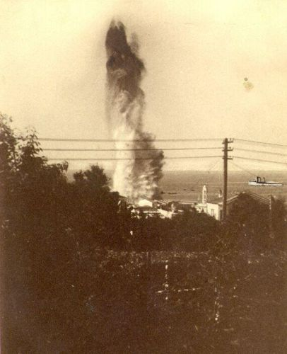 Η στιγμή της έκρηξης μιας εκ των τορπιλών στην προβλήτα του λιμανιού της Τήνου, στις 15 Αυγούστου 1940. Η Έλλη διακρίνεται στην δεξιά πλευρά του στύλου.