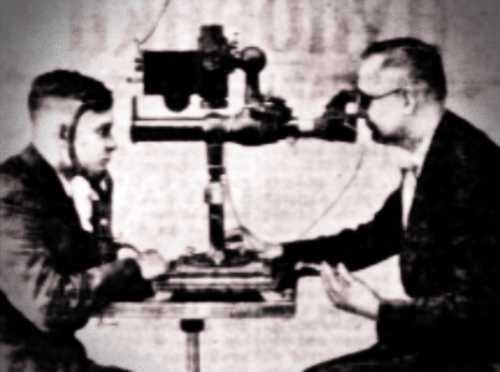 Ο Δόκτωρ Νόρτενζεν (δεξιά) μπροστά από την εφεύρεσή του, φωτογραφίζοντας το εσωτερικό του οφθαλμού ενός βοηθού του