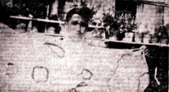 Ο Μιχάλης Ανδριανίτης, βαστώντας ένα τραπεζομάντηλο, που καταστράφηκε από αυτόματη ανάφλεξη. Διακρίνονται οι οπές που προκλήθηκαν από τη φωτιά.